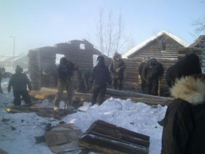 Volunteers in Huslia tear down the old mission building to distribute wood to people who need it. Photo by Nathan Vent