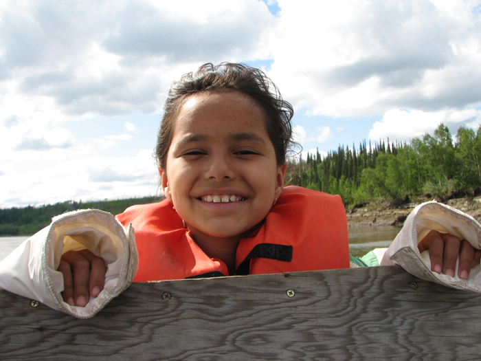 My daughter enjoys a boat ride along the Koyukuk River. The mosquitoes blow away in the wind. Photo by Angela Gonzalez