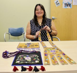 Athabascan Artist Brenda Mahan with her latest pieces of beadwork include a firebag, wall hanging and moose hide octopus bag. Photo by Angela Gonzalez