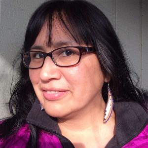 Angela Gonzalez wears earrings made by Athabascan Artist Brenda Mahan